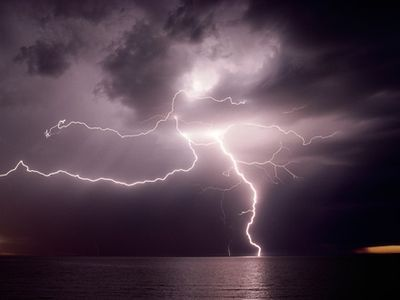 Photo: Dramatic lightning flashes over water