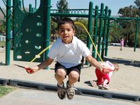 Photo: Boy jumps rope at a playground.