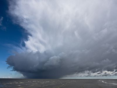 Photo: Storm clouds and rain gathers over an area of shallow sea.