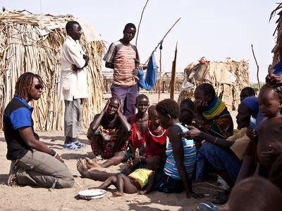 Photo: African people sit in a rural village.