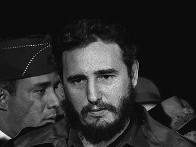 Young Fidel Castro stands in front of a bank of microphones.