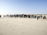 Dozens of people walk across a sandy lake bed on a sunny day.