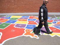Photograph of man walking over U.S. map chalk drawing on sidewalk.