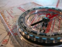 Photograph of a compass, ruler and map.