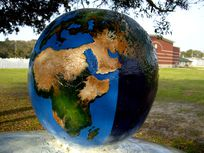 Photograph of a globe on a lawn.