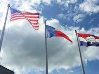 Photograph of flags blowing in the wind.