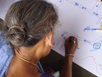 Photograph of a woman participating in a public participatory mapping project in India.
