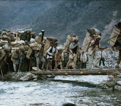 Men cross a bridge made of two logs as they hike to base camp on Mount Everest in 1963 in preparation for an American team to attempt to summit.