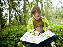 Girl with herbarium in the woods