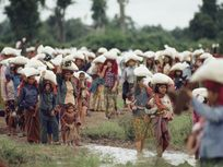 Piteous procession of homeless Cambodians carry bags of UNICEF rice.