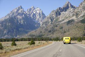 yellow van traveling through the Grand Tetons