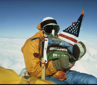 Mount Everest, Nepal. May 1, 1963, James Whittaker, the first American to summit Mount Everest, poses with the United States and National Geographic flags.