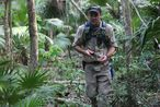 Picture of Dominique Rissolo using a handheld GPS receiver in the forest of Quintana Roo