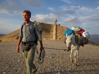 A journalist leads his mule past a royal tomb near Nemrut in eastern Turkey during his Out of Eden Walk, a seven-year global trek from Africa to Tierra del Fuego.
