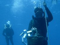 In the Mediterranean Sea off the Coast of Turkey, a diver rises from a Byzantine wreck with a basket full of artifacts.