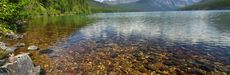 Brightly colored rocks seen through the crystal clear waters of Kintla Lake in Glacier National Park - USA.