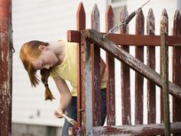 Caucasian girl painting fence