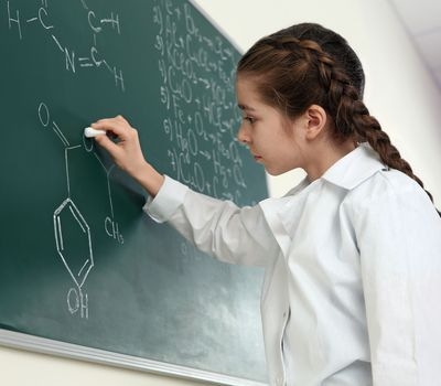 Schoolgirl writing chemistry formula on blackboard in class; Shutterstock ID 1448129384; Project details: National Geographic Education Resource Library ; Job: National Geographic Education Resource Library; Client/Licensee: National Geographic Society; Other: Carbon Tracker Unit