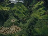 Airplane drops rice and corn above refugee village amid rugged hills.