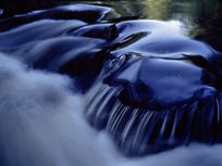 A photograph of water flowing over rocks in the rapids of Shenandoah River.