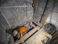 A restoration worker carefully brushes sediment away in the Church of the Holy Sepulchre in Jerusalem's old city.