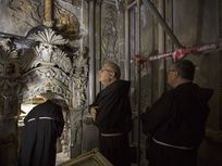 Three men inspect ongoing renovations of the Church of the Holy Sepulchre in Jerusalem's old city.