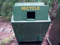 A Photograph of a green recycling bin located in Redwood National and State Parks.