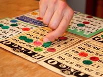 Person playing bingo, placing winning piece on bingo card, close-up