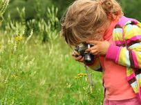 Little girl photographs flower outdoors