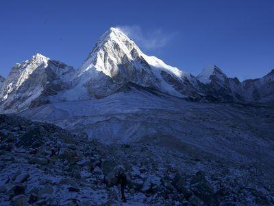 The peak of Mount Everest, highest point on Earth, illuminated by the sun.