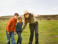 Hispanic female park ranger pointing for children
