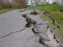 Photo of a road with cracks from a quake.