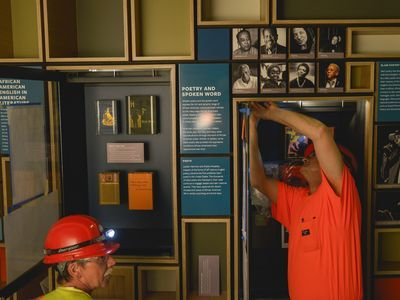 Construction workers install an exhibit at the Smithsonian's National Museum of African American History and Culture (NMAAHC) prior to its opening in 2016.