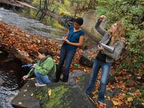 a photograph of three students sampling water in Rock Creek Park, District of Columbia.