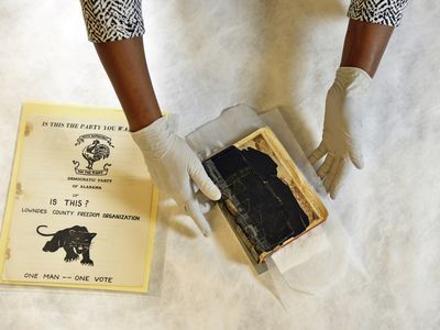 Renee Anderson, head of collections at the National Museum of African American History and Culture (NMAAHC), cautiously sets the Bible of a Buffalo Soldier from 1913 and a pamphlet for the Black Panther Party from 1966 on a table. These artifacts were selected for exhibits in NMAAHC.