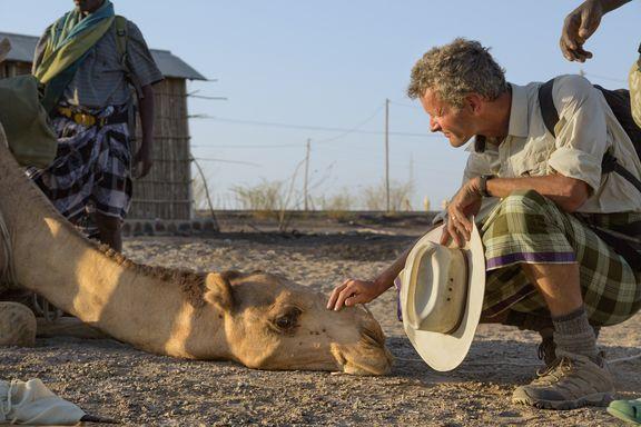 paul salopek pets a kneeling camel