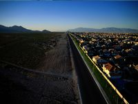 A paved road divides a new housing development from the natural desert valley of Las Vegas.