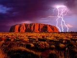 <p>Photo: Lightning striking next to large red rock</p>
