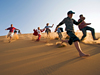 Picture of a family running down a sand dune in the Namib Desert
